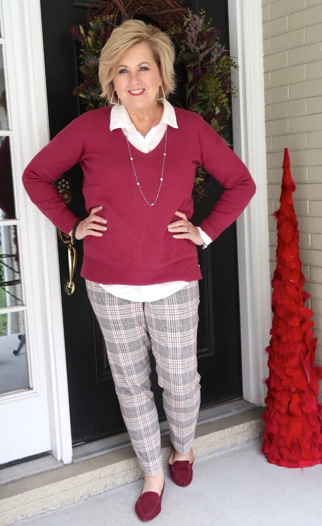 Fashion Blogger 50 Is Not Old is wearing a magenta v neck sweater in a solid color and plaid pants