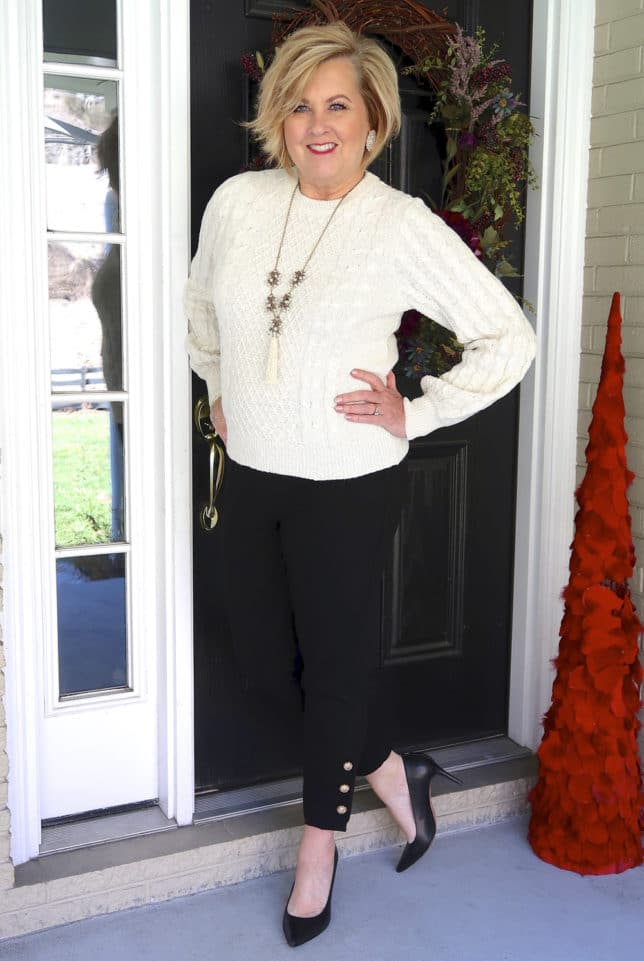 Ivory sweater with black pants with embellishments on the hem