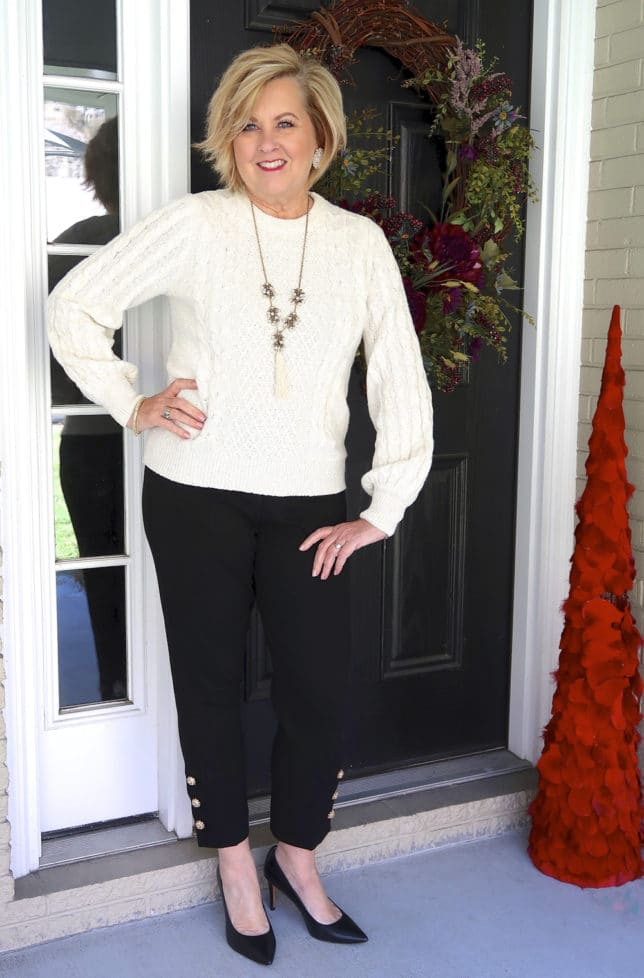 Ivory cable knit sweater and black pants with embellishments on the hem from Chico's worn by fashion blogger 50 is not old