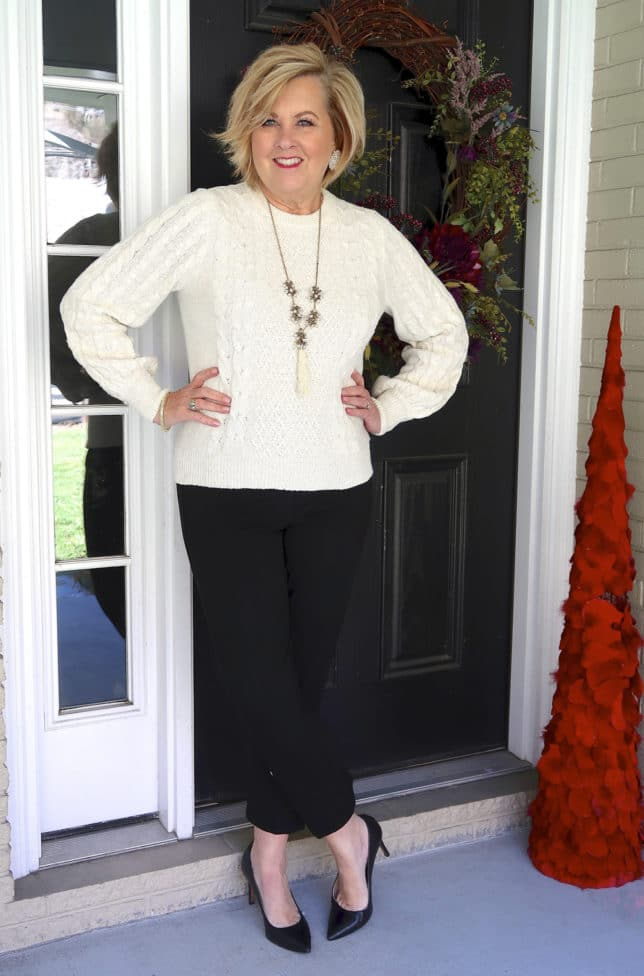 Ivory cable knit sweater and black pants with embellishments on the hem and black pumps worn by fashion blogger 50 is not old