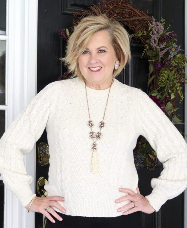 Ivory cable knit sweater worn by fashion blogger 50 is not old