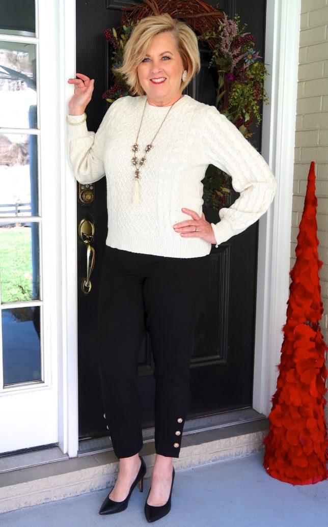 Ivory cable knit sweater and black pants with embellishments on the hem worn by fashion blogger 50 is not old