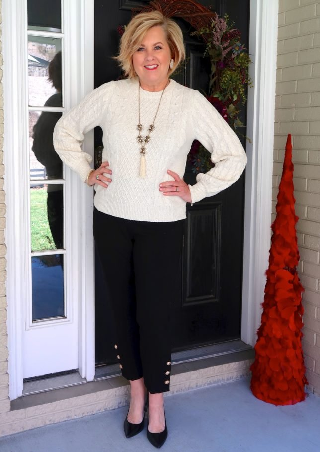 Ivory sweater with black pants with embellishments on the hem worn by fashion blogger 50 is not old