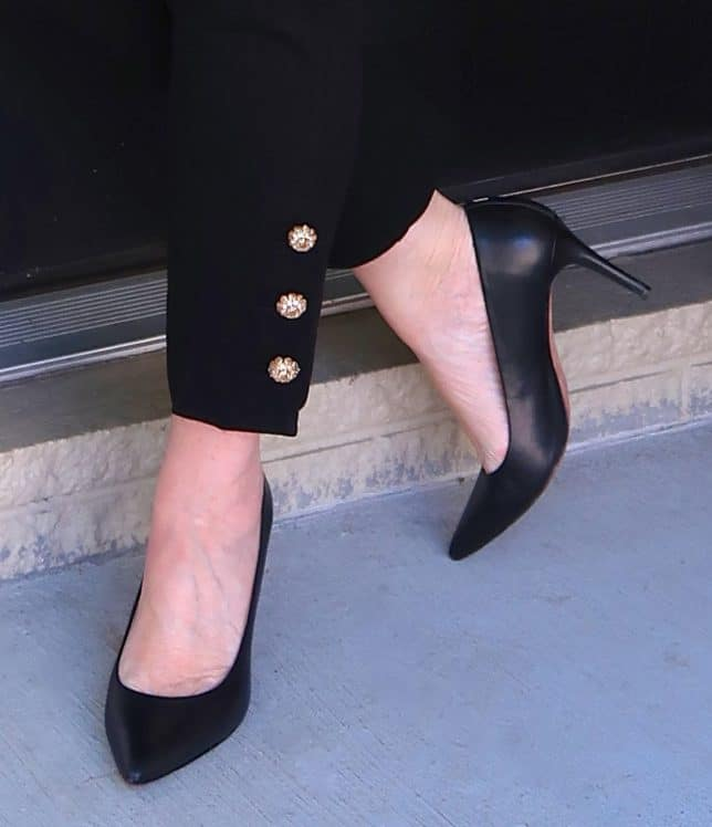 black pants with embellishments on the hem and black pumps from Coach worn by fashion blogger 50 is not old