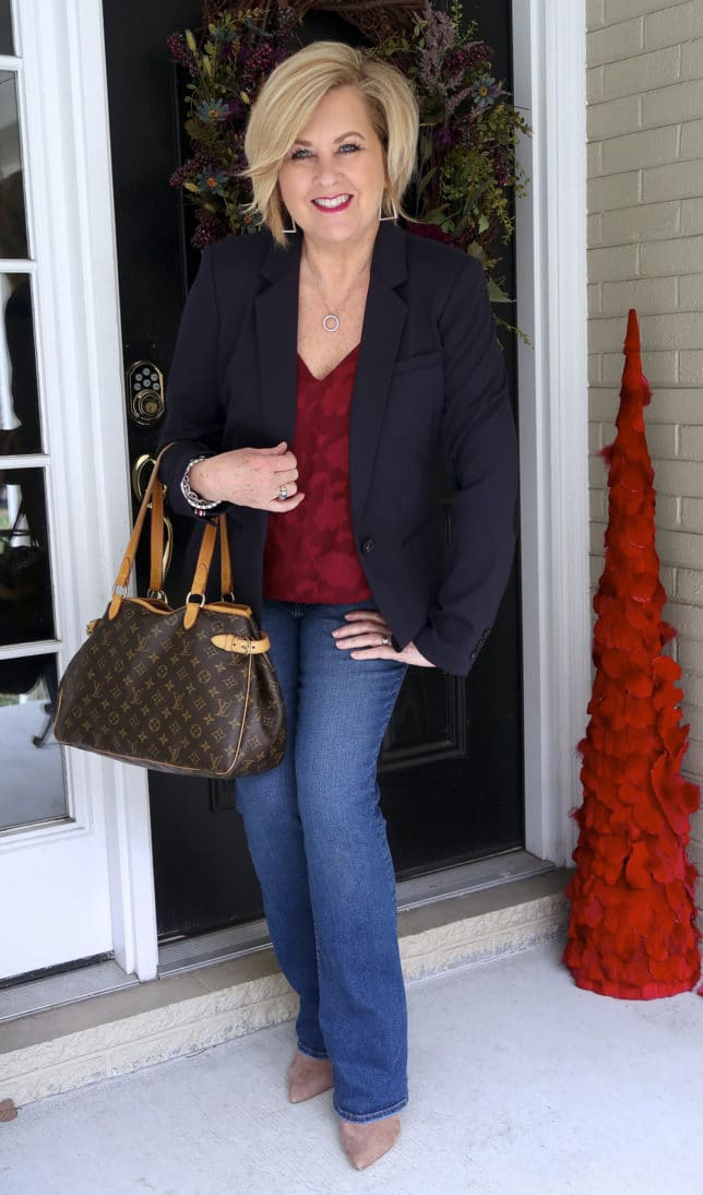 Flare jeans, pointy boots, a floral burgundy camisole, a Louis Vuitton satchel, and a navy blazer makes a great look