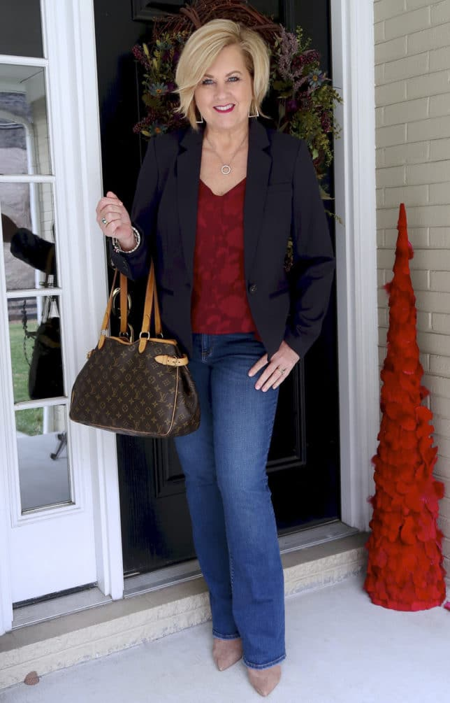 Flare jeans, pointy boots, a burgundy camisole, and a navy blazer makes a great look