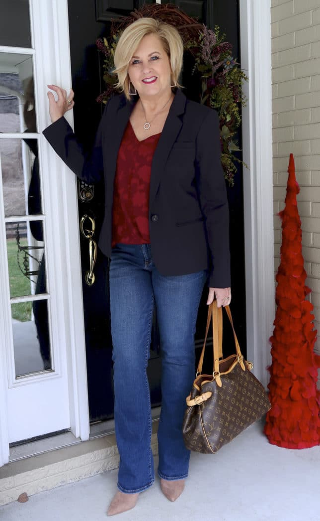 In January Fashion Blogger 50 Is Not Old wearing a navy blazer with a burgundy floral cami and boot cut jeans