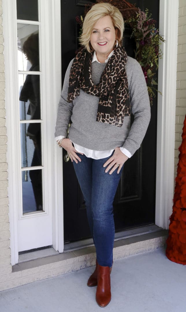 Fashion Blogger 50 Is Not Old is mixing a classic gray cashmere sweater, jeans, and a trendy leopard scarf