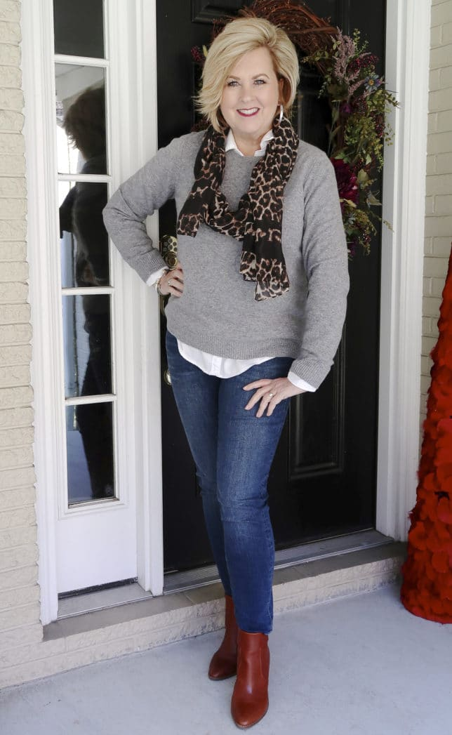 Fashion Blogger 50 Is Not Old is mixing a classic cashmere sweater, skinny jeans, ankle boots, and a trendy leopard scarf