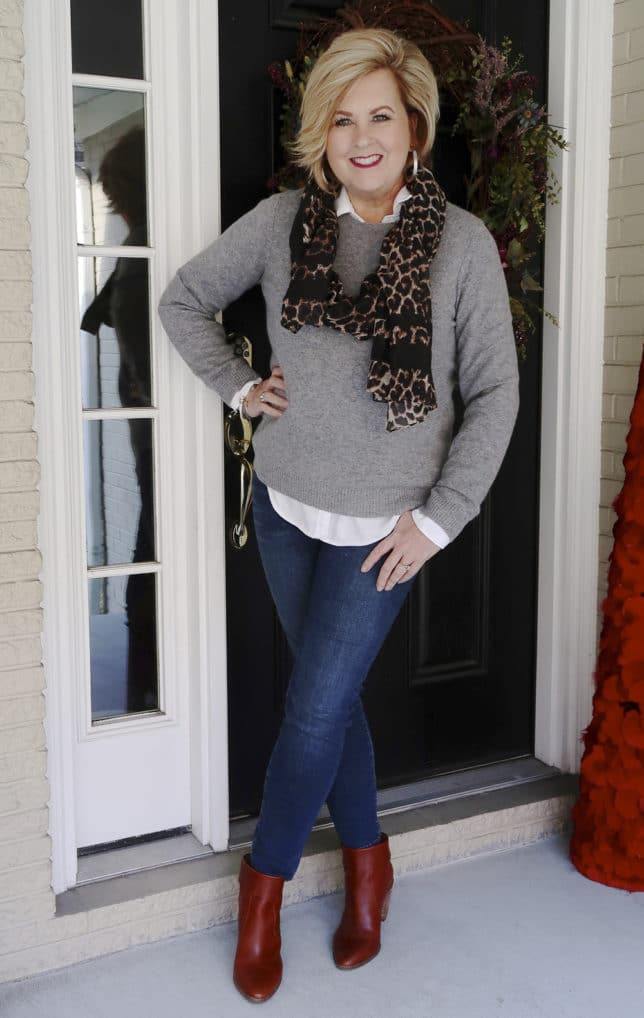 Fashion Blogger 50 Is Not Old is mixing a classic cashmere sweater, skinny jeans, and a trendy leopard scarf