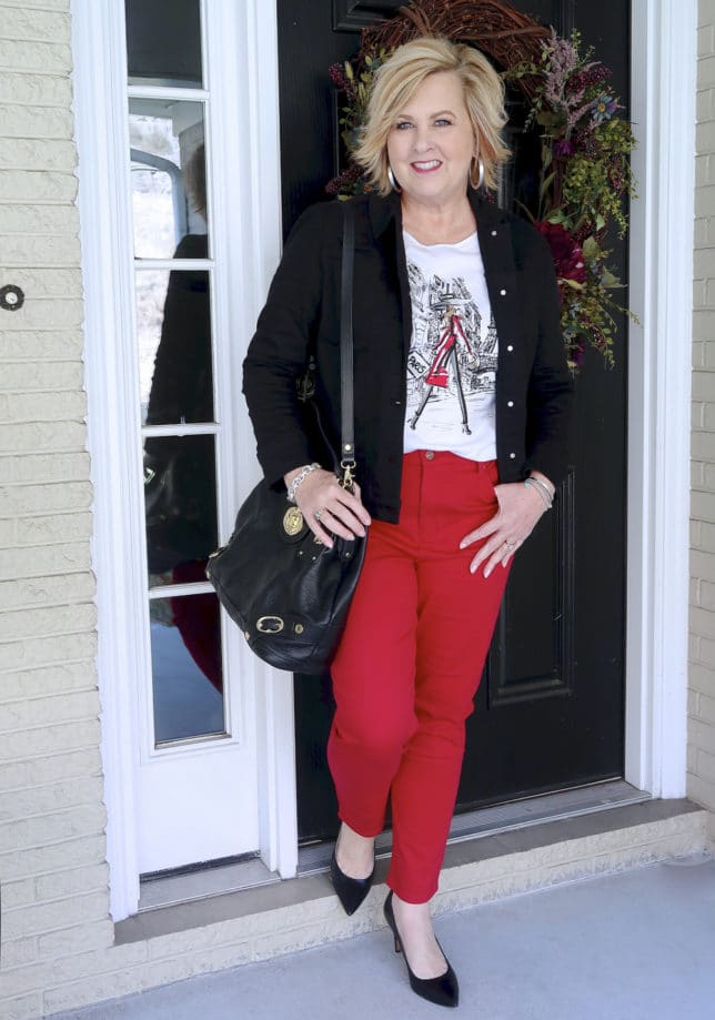 FASHION BLOGGER 50 IS NOT OLD IS WEARING A BLACK DENIM JACKET AND RED PANTS FROM CHICO'S WITH A PAIR OF BLACK PUMPS AND A BLACK LEATHER HANDBAG