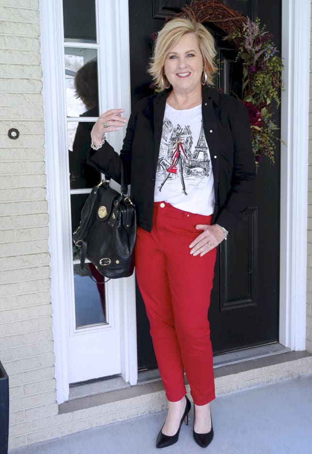 FASHION BLOGGER 50 IS NOT OLD IS WEARING A BLACK DENIM JACKET AND RED PANTS FROM CHICO'S WITH A BLACK LEATHER HANDBAG
