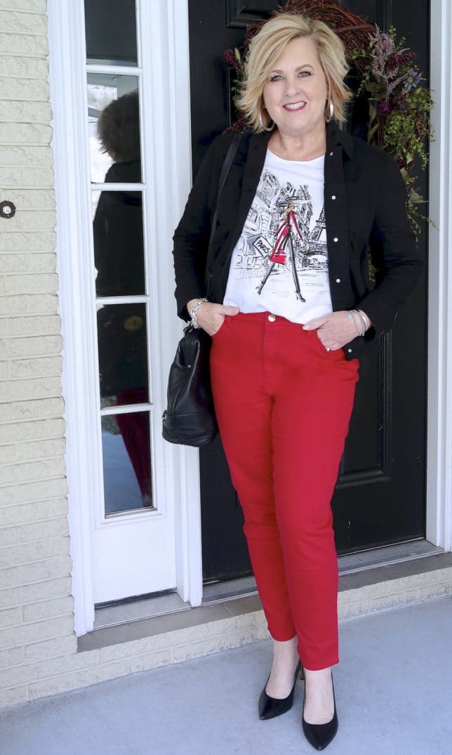 FASHION BLOGGER 50 IS NOT OLD IS WEARING A BLACK DENIM JACKET, A GRAPHIC TEE AND RED PANTS FROM CHICO'S