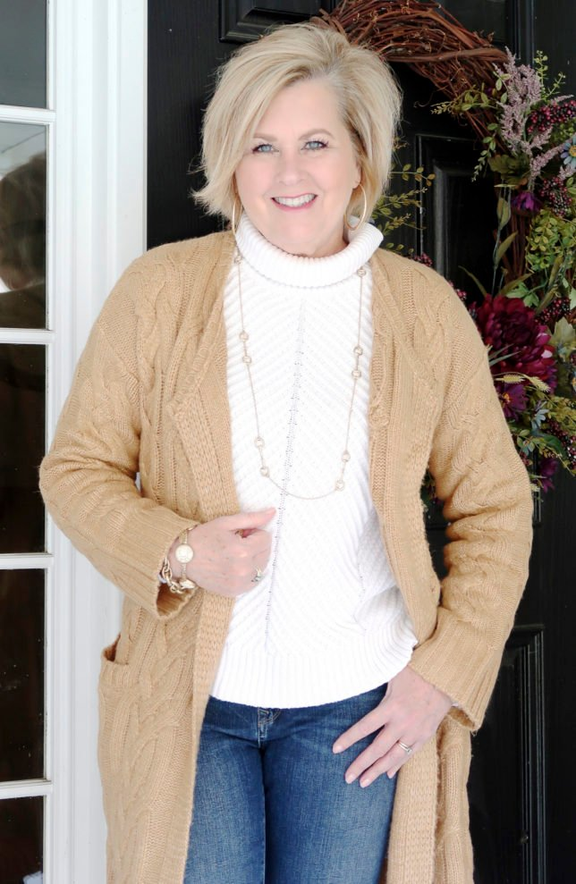 Fashion Blogger 50 Is Not Old is wearing a neutral cable knit cardigan in tan and a white turtleneck sweater