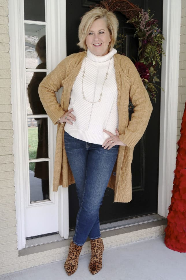 Fashion Blogger 50 Is Not Old is wearing a neutral cable knit cardigan in tan, jeans, and animal print ankle boots