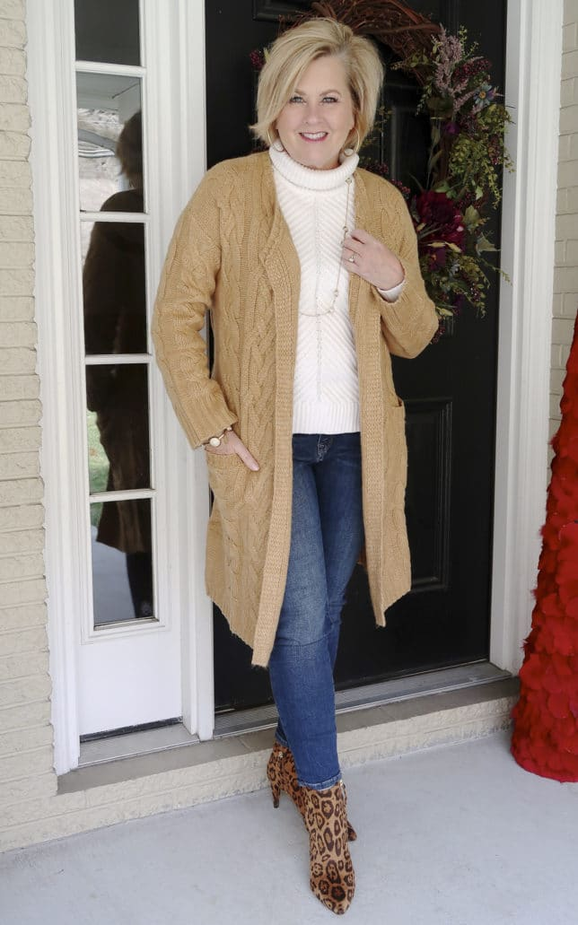 Fashion Blogger 50 Is Not Old is wearing a neutral cable knit cardigan in tan and jeans