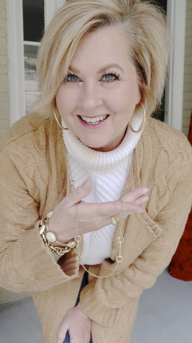 Fashion Blogger 50 Is Not Old is wearing a neutral cable knit cardigan in tan and showing gold jewelry