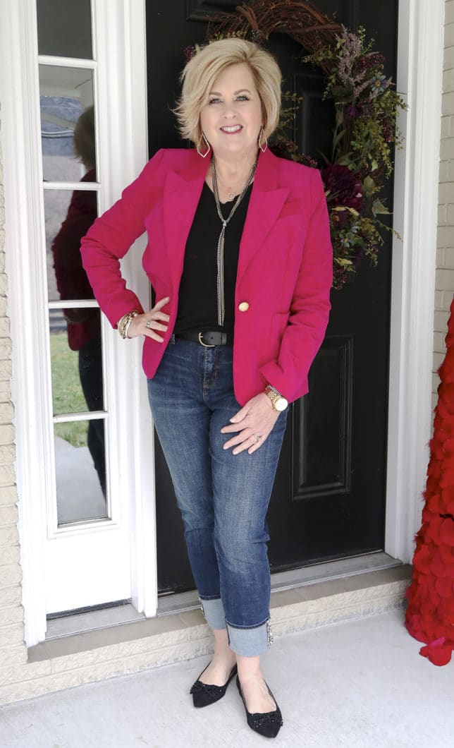 Bright pink jacket, a black t-shirt and jean worn by Fashion Blogger 50 Is Not Old