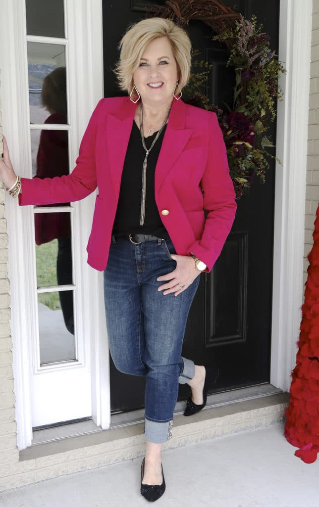 Bright pink jacket with a black t-shirt, cuffed jeans, and black flats worn by Fashion Blogger 50 Is Not Old