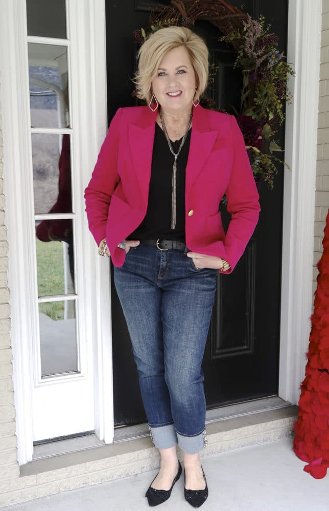 Bright pink jacket with a black t-shirt and belted jean worn by Fashion Blogger 50 Is Not Old