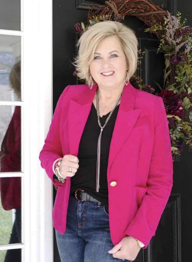 Bright pink jacket with a black t-shirt and gold jewelry worn by Fashion Blogger 50 Is Not Old