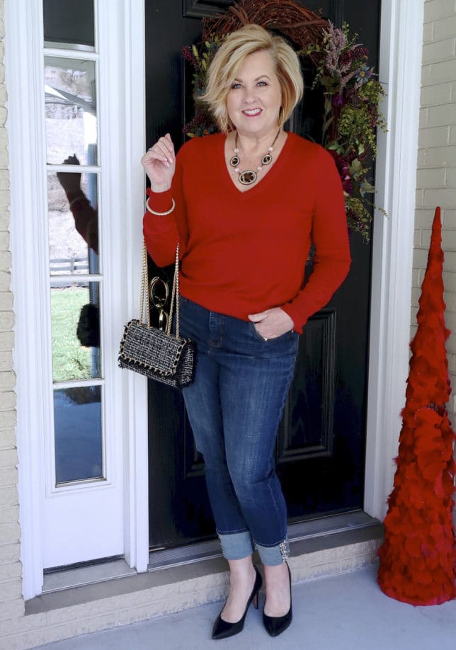 Jeans with a tweed cuff, black flats, and a red v neck sweater worn by Fashion Blogger 50 Is Not Old