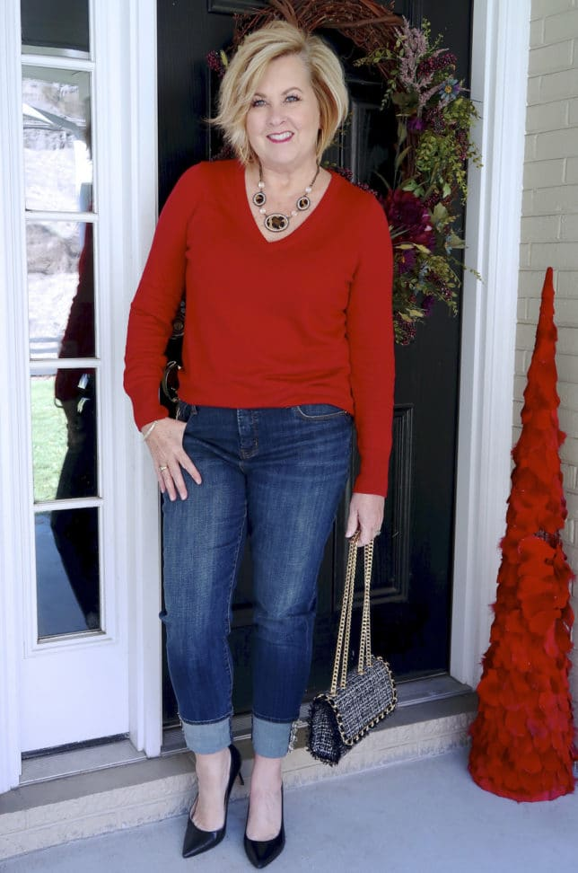 Jeans with a tweed cuff, a tweed handbag, and a red v neck sweater worn by Fashion Blogger 50 Is Not Old