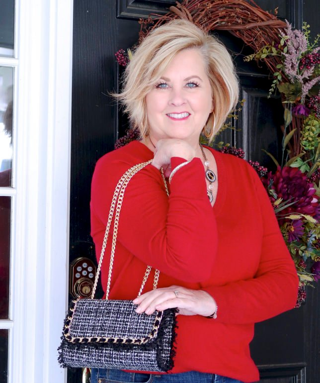 a tweed handbag from Chicos and a red v neck sweater worn by Fashion Blogger 50 Is Not Old