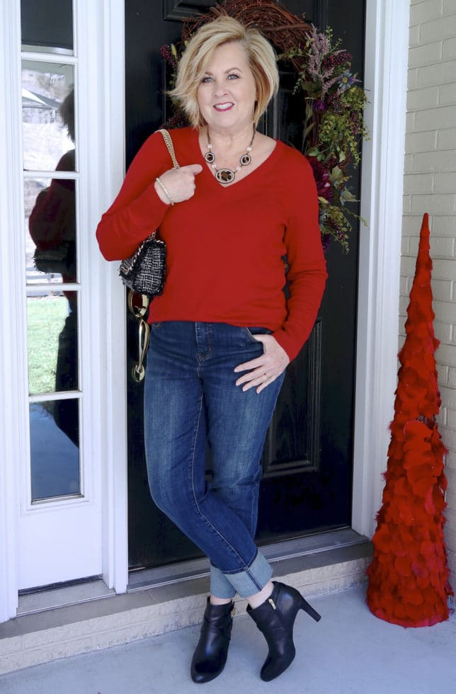 Jeans with a tweed cuff, black ankle boots, and a red v neck sweater worn by Fashion Blogger 50 Is Not Old
