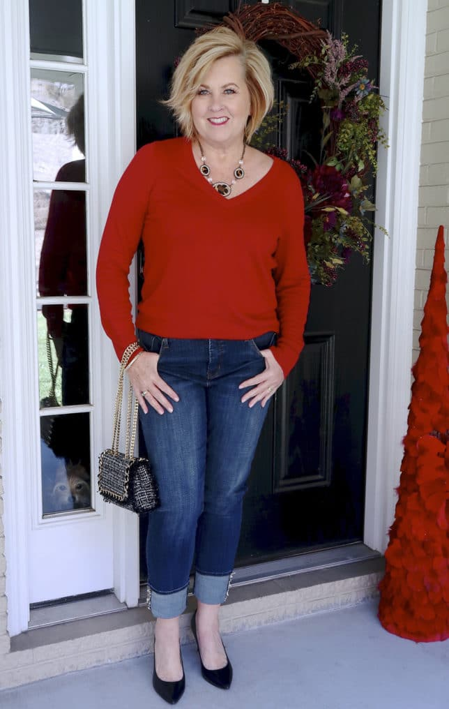 Jeans with a tweed cuff, black pumps, and a red v neck sweater worn by Fashion Blogger 50 Is Not Old
