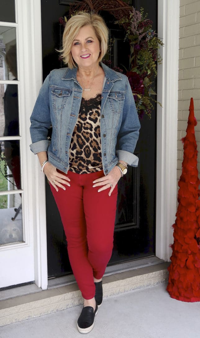 For the month of love, fashion blogger 50 Is Not old is wearing red jeans, a leopard cami, and a denim jacket
