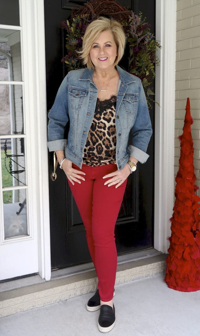For the month of love, fashion blogger 50 Is Not old is wearing red jeans, a leopard camisole, and a denim jacket