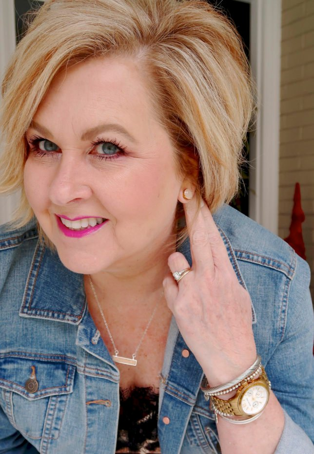 Fashion blogger 50 Is Not old is wearing a denim jacket with Kate Spade stud earrings