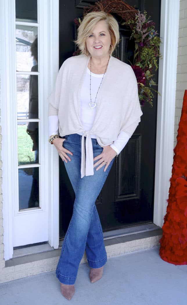Fashion Blogger 50 Is Not Old wearing a tie wrap cardigan from Chicos and flare jeans