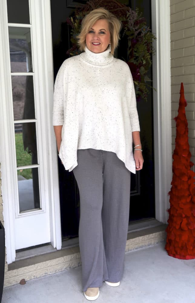 50 Is Not Old is traveling in comfort with this poncho sweater and lounge pants with wedge sneakers