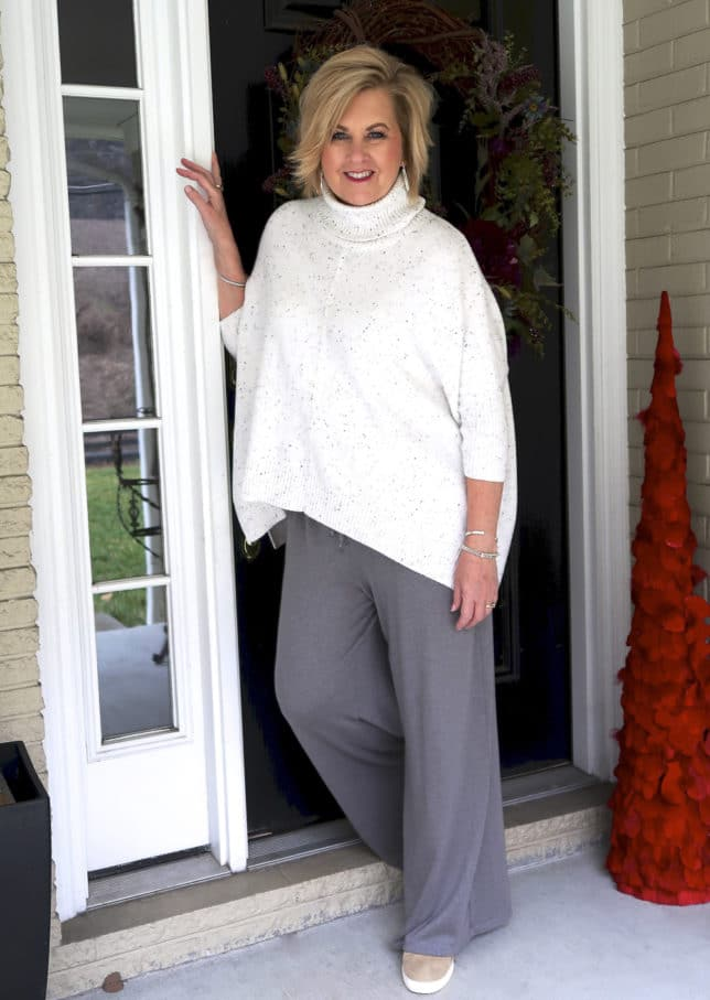 50 Is Not Old is traveling in comfort with this poncho sweater and gray lounge pants from Fabletics
