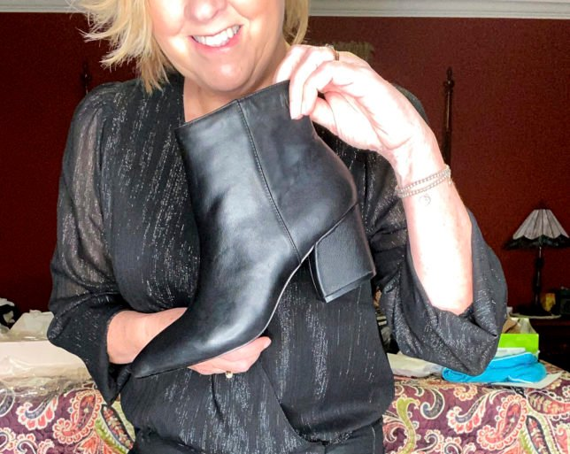 A pair of black leather boots with a chunky heel shown by fashion blogger 50 Is Not Old