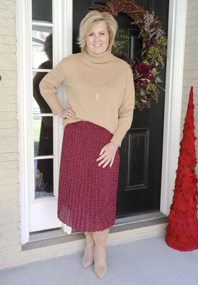 A classic turtleneck sweater with a burgundy skirt and knee boots worn by fashion blogger 50 Is Not Old
