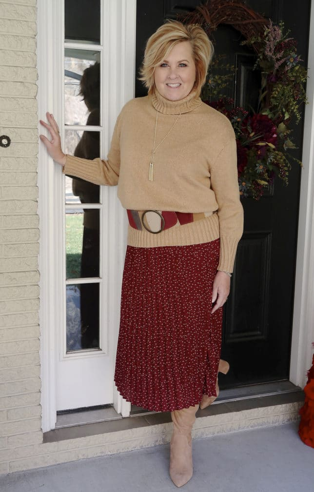 A classic turtleneck sweater belted with a burgundy skirt and knee boots worn by fashion blogger 50 Is Not Old