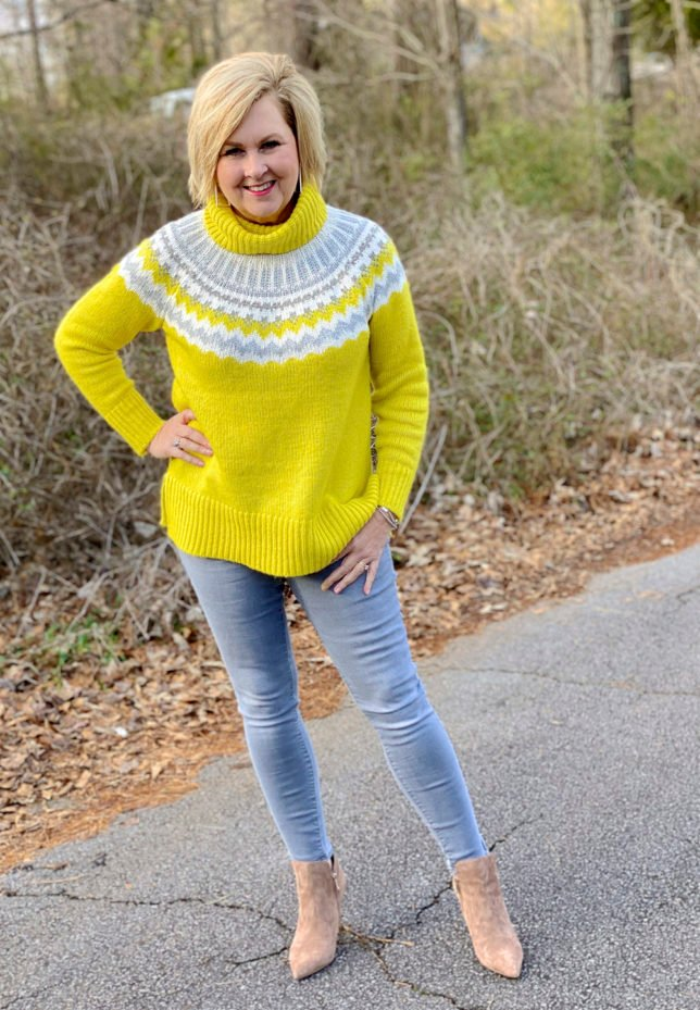 Fashion Blogger 50 Is Not Old wearing a yellow turtleneck sweater and gray skinny jeans