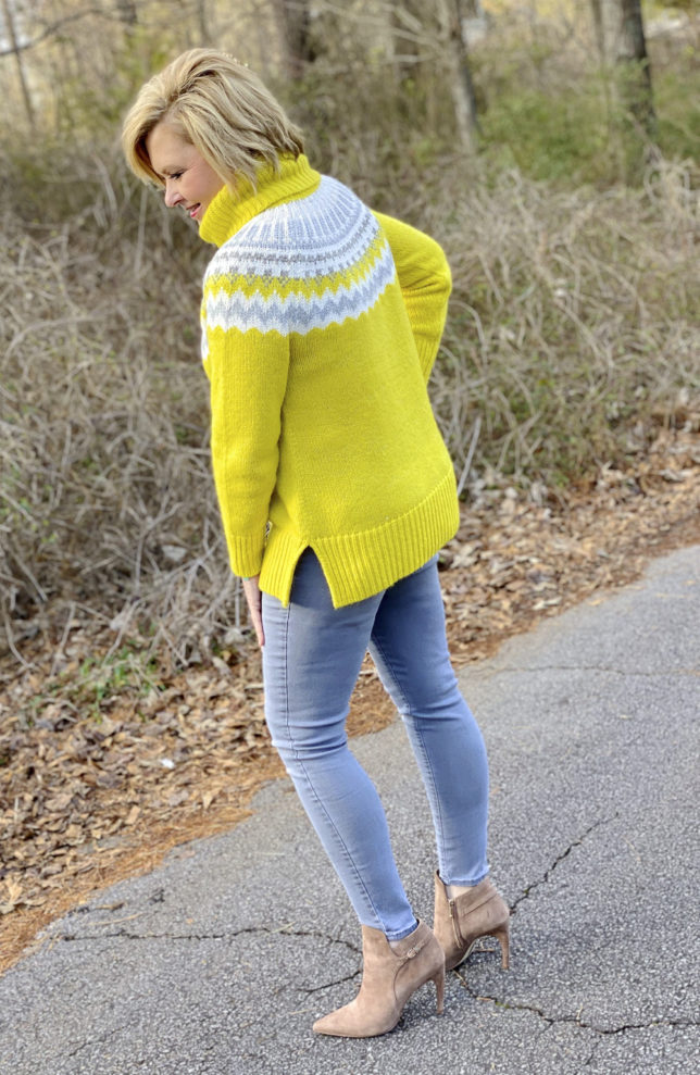 Fashion Blogger 50 Is Not Old wearing a yellow turtleneck sweater and gray skinny jeans with ankle boots