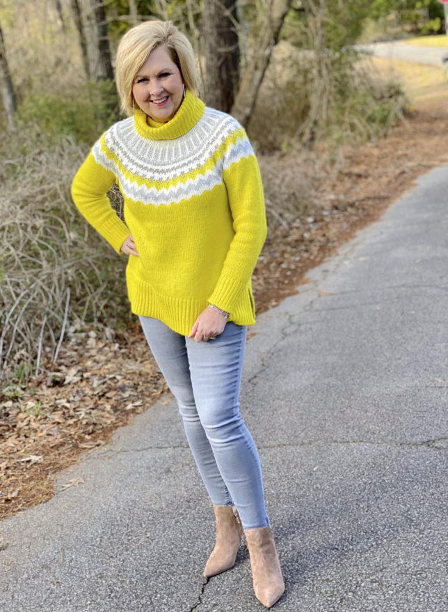 Fashion Blogger 50 Is Not Old wearing a yellow turtleneck sweater and gray skinny jeans with neutral ankle booties