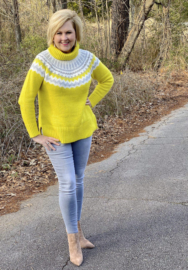 Fashion Blogger 50 Is Not Old wearing a yellow turtleneck sweater and gray skinny jeans with neutral ankle boots
