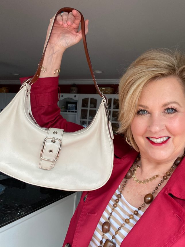 Fashion Blogger 50 Is Not Old holding an ivory Coach handbag