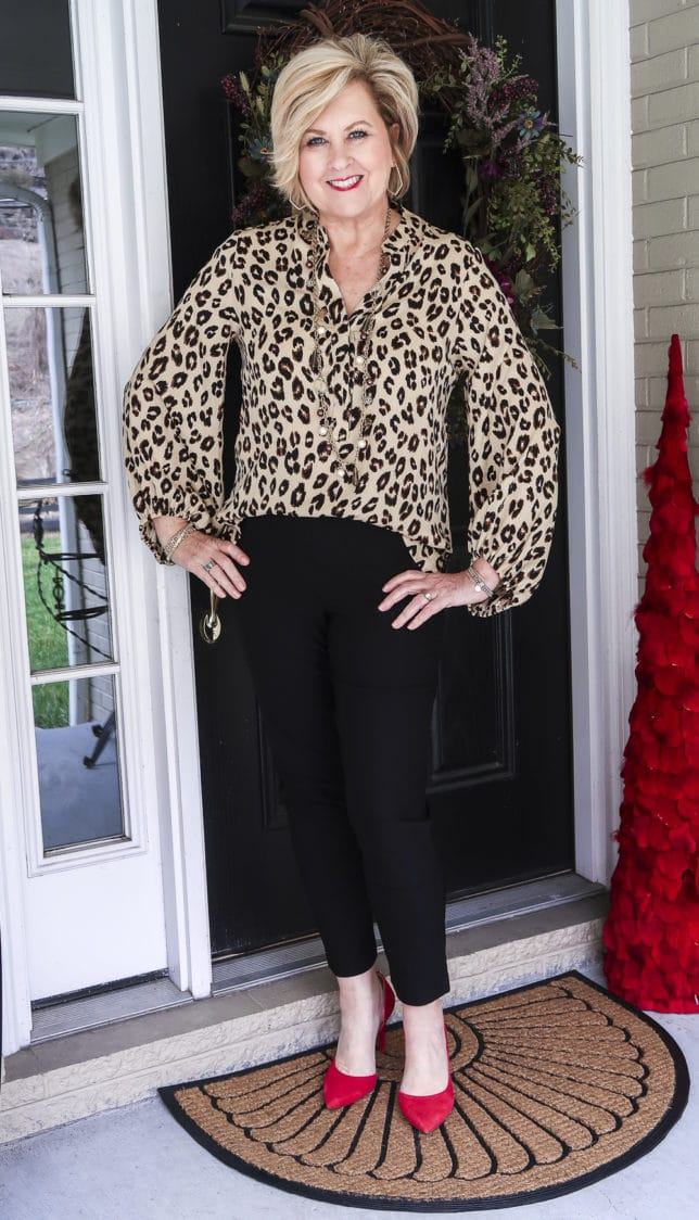 Fashion Blogger 50 Is Not Old is wearing the perfect leopard print top with a pair of black ankle pants and red pumps