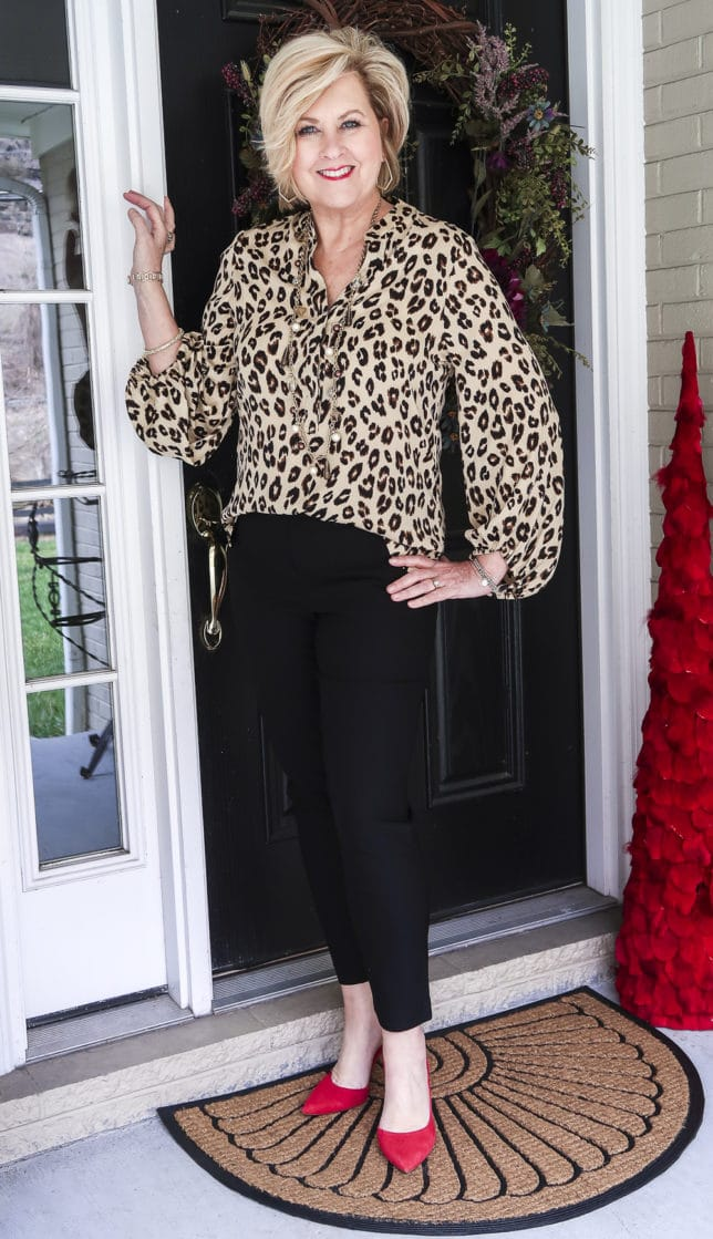 Fashion Blogger 50 Is Not Old is wearing the perfect leopard print top with a pair of black ankle pants and red suede pumps