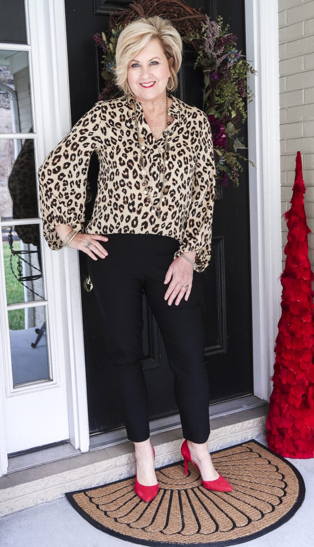 Fashion Blogger 50 Is Not Old is wearing the perfect leopard print top from Chico's with a pair of black ankle pants and red suede pumps