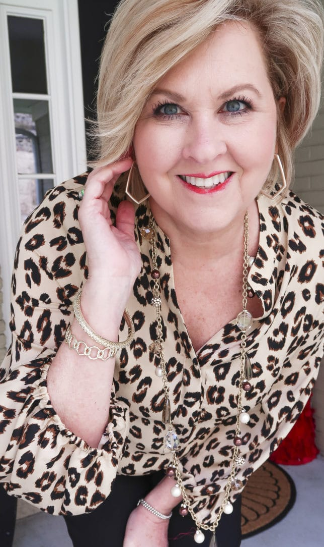 Fashion Blogger 50 Is Not Old is wearing the perfect leopard print top with gold jewelry from Kendra Scott