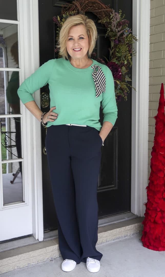 Fashion Blogger 50 Is Not Old wearing a light Jade sweater with a striped scarf with navy wide leg pants.
