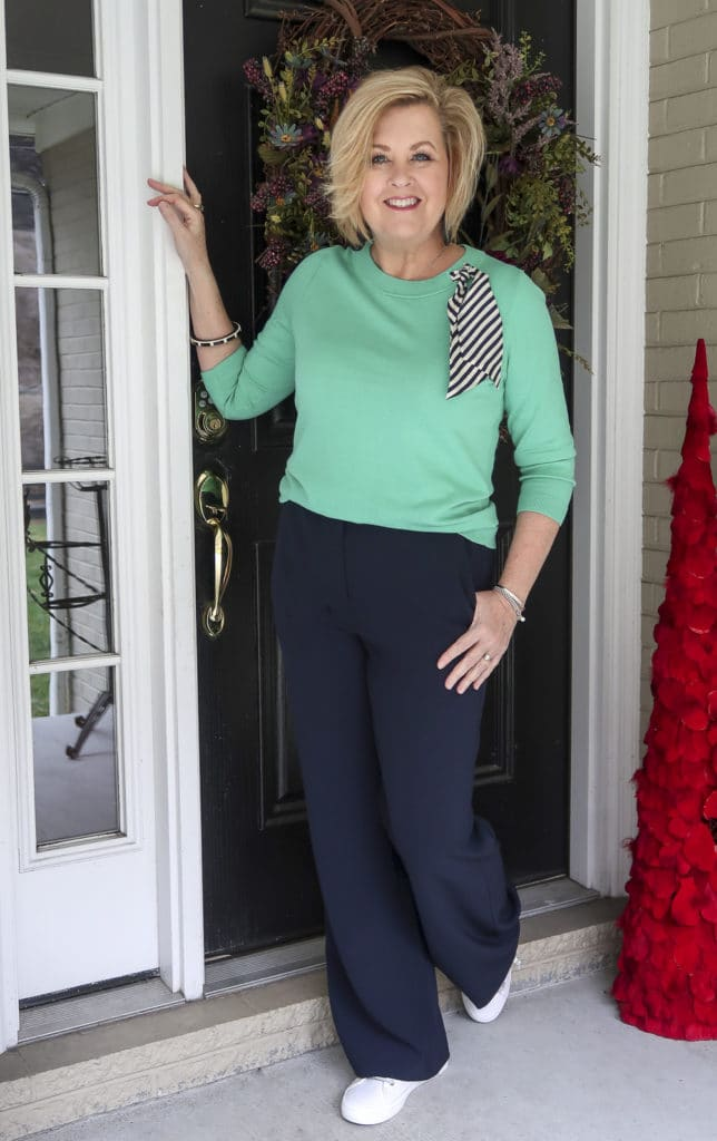 Fashion Blogger 50 Is Not Old wearing a Jade sweater with a silk scarf with navy wide leg pants with sneakers